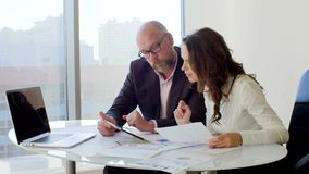 Due genti di affari che lavorano con la compressa Essi che discutono le idee di affari che si siedono sulle sedie nell'ufficio le archivi video