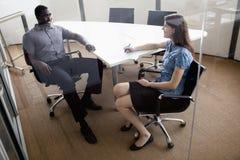 Due genti di affari che si siedono ad una tavola di conferenza e che discutono nel corso di una riunione d'affari Immagine Stock