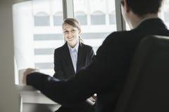 Due genti di affari che si siedono, sorridenti ed esaminantese nel corso di una riunione d'affari Immagine Stock