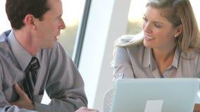 Due genti di affari con il computer portatile che ha riunione stock footage