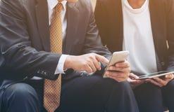 Due genti di affari discutono l'affare di affari sul telefono cellulare Immagini Stock