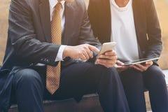 Due genti di affari discutono l'affare di affari sul telefono cellulare Fotografie Stock Libere da Diritti