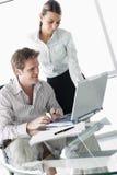 Due genti di affari in sala del consiglio con il computer portatile Immagine Stock Libera da Diritti