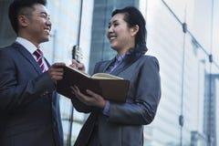 Due genti di affari sorridenti fuori della riunione e della scrittura nell'organizzatore personale Fotografie Stock Libere da Diritti