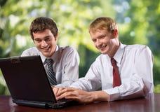 Due genti di affari sul computer portatile Fotografia Stock Libera da Diritti