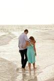 Due genti muniscono in braccio che camminano attraverso l'oceano Fotografia Stock Libera da Diritti