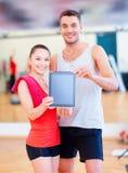 Due genti sorridenti che mostrano lo schermo in bianco del pc della compressa Fotografia Stock