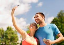 Due genti sorridenti con gli smartphones all'aperto Fotografie Stock
