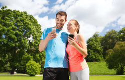 Due genti sorridenti con gli smartphones all'aperto Immagine Stock Libera da Diritti