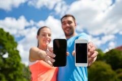 Due genti sorridenti con gli smartphones all'aperto Immagini Stock