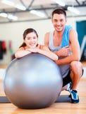 Due genti sorridenti con la palla di forma fisica Fotografia Stock