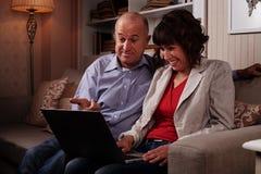 Due genti sorridenti piacevoli che guardano qualcosa sul computer portatile Fotografie Stock
