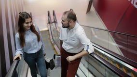 Due genti sulla scala mobile nel centro commerciale stock footage