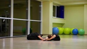 Due ginnaste artistiche delle sorelle sveglie esili delle ragazze in abiti sportivi neri fare riscaldamento in palestra ed esegui