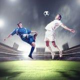 Due giocatori di football americano che direzione la palla Immagini Stock Libere da Diritti