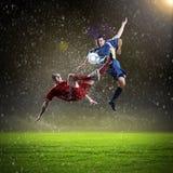 Due giocatori di football americano che colpiscono la palla Immagini Stock