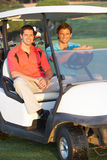 Due giocatori di golf maschii che guidano in Buggy di golf Immagini Stock Libere da Diritti