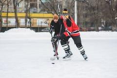 Due giocatori di hockey feroci che combattono per il disco Fotografie Stock Libere da Diritti