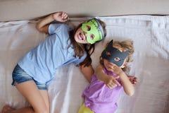 Due giochi delle ragazze lo sciocco in un mostro della maschera per il gatto nero di Halloween Fotografie Stock Libere da Diritti
