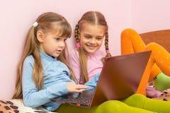 Due giochi di computer del gioco delle ragazze sul computer portatile Fotografie Stock Libere da Diritti
