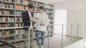 Due giovane studente Searching Information in libro in biblioteca stock footage