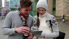 Due giovani adulti facendo uso di una compressa all'aperto video d archivio