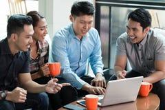Due giovani allegri che per mezzo di un computer portatile mentre dividendo le idee di affari Immagini Stock Libere da Diritti