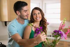 Due giovani amanti ridono e giocano nella felicità che mette amoroso i fiori dal loro giardino in un vaso Fotografia Stock