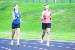 Due giovani amiche caucasiche in abiti sportivi atletici che hanno esercizi pareggianti Fotografia Stock
