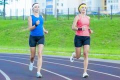 Due giovani amiche caucasiche in abiti sportivi atletici che hanno esercizi pareggianti intorno alla sede di sport Fotografia Stock Libera da Diritti