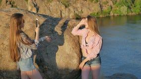 Due giovani amiche con uno smartphone sulla roccia stock footage