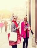 Due giovani amici femminili attraenti che godono di un acquisto di giorno di vacanza, immagine colorised immagini stock