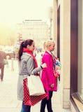 Due giovani amici femminili attraenti che godono di un acquisto di giorno di vacanza, immagine colorised fotografia stock libera da diritti