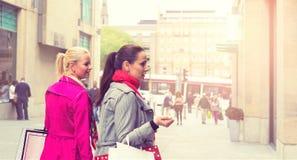Due giovani amici femminili attraenti che godono di un acquisto di giorno di vacanza, immagine colorised immagine stock libera da diritti