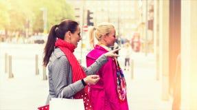 Due giovani amici femminili attraenti che godono di un acquisto di giorno di vacanza, immagine colorised fotografia stock