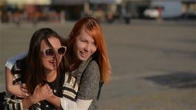 Due giovani amici femminili delle ragazze che danno sulle spalle sulla vacanza che ride e che cammina nella città, giorno soleggi archivi video