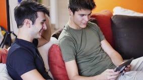Due giovani amici maschii che per mezzo del computer della compressa Fotografie Stock