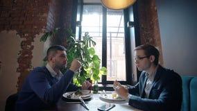 Due giovani amici stanno mangiando l'alimento, parlare, sedentesi alla tavola in ristorante, persone di affari sono a pranzo di l archivi video