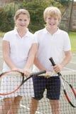 Due giovani amici sul sorridere della corte di tennis Fotografie Stock Libere da Diritti