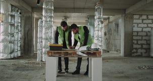 Due giovani architetti che fanno programma di lavoro per il cantiere stock footage