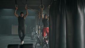 Due giovani atletici che dowing tirata-UPS insieme nella palestra spaziosa movimento lento 4k stock footage