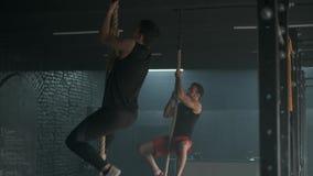 Due giovani atletici che dowing tirata-UPS sulla corda che scala insieme nella palestra spaziosa movimento lento 4k video d archivio