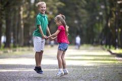 Due giovani bambini sorridenti divertenti svegli, ragazza e ragazzo, fratello e sorella, saltanti e divertentesi sul vicolo soleg fotografia stock