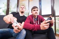 Due giovani bei che giocano i video giochi mentre sedendosi sul sofà Fotografie Stock