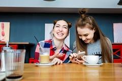 Due giovani belle donne dei pantaloni a vita bassa che si siedono al caffè, attrezzatura d'avanguardia alla moda, vacanza di Euro Fotografie Stock