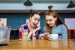 Due giovani belle donne dei pantaloni a vita bassa che si siedono al caffè, parlando, attrezzatura d'avanguardia civettuola e all Immagine Stock