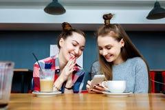 Due giovani belle donne dei pantaloni a vita bassa che si siedono al caffè, parlando, attrezzatura d'avanguardia civettuola e all Immagini Stock