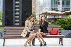 Due giovani belle donne di affari che si siedono su un banco Fotografie Stock