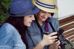 Due giovani belle ragazze in vestiti e cappelli dai jeans si siedono su un banco nel parco su un fondo delle pareti della pianta  Fotografie Stock