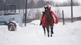 Due giovani brunettes in vestiti che galoppano velocemente su un cavallo attraverso il campo innevato nell'inverno stock footage